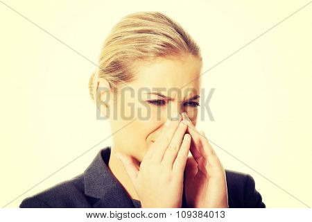 Woman pinching her nose because of disgusting smell.