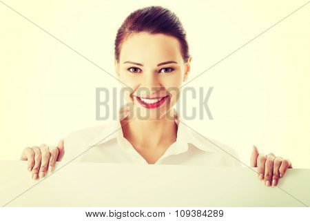Happy woman holding white empty banner.
