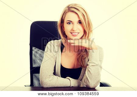 Happy woman sitting at the desk touching chin.