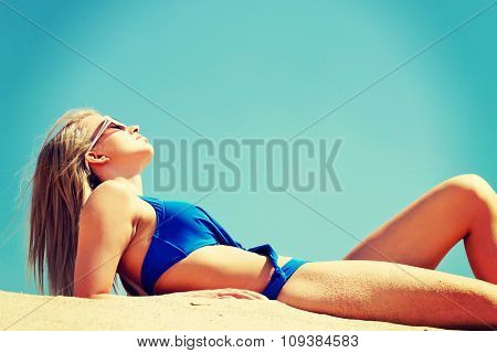 Photo of a woman lying on the beach.