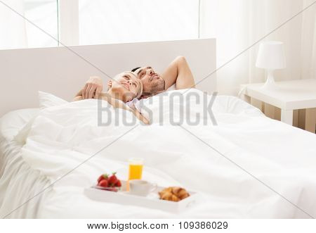 people, love, care and happiness concept - happy couple lying in bed with tray of breakfast at home
