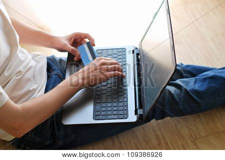 Man shopping online using laptop at home