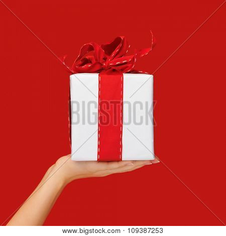 people, holidays, present, surprise and birthday concept - close up hand holding christmas gift box over red background