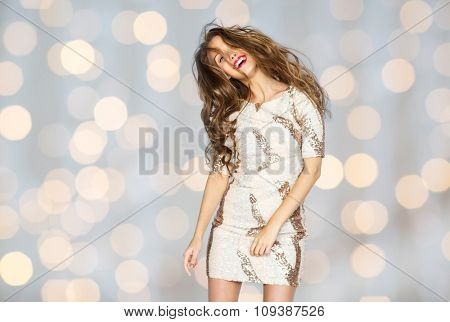 people, style, holidays, hairstyle and fashion concept - happy young woman or teen girl in fancy dress with sequins and long wavy hair dancing at party over lights background