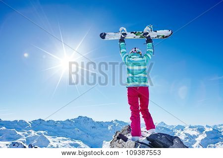Back view of female snowboarder wearing colorful helmet, blue jacket, grey gloves and pink pants standing with snowboard raised overhead and enjoying sunnymountain landscape - winter sports concept