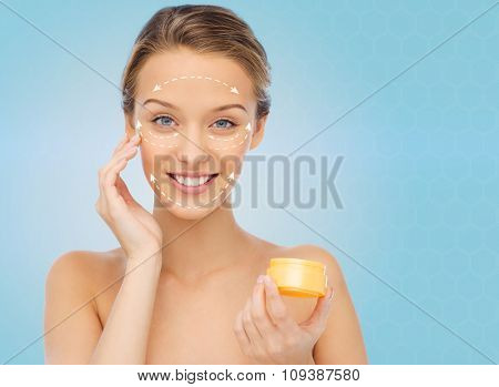 beauty, people, cosmetics, skincare and anti-aging concept - happy young woman applying cream to her face with white arrows over blue background