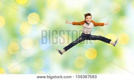 happiness, childhood, freedom, movement and people concept - happy smiling boy jumping in air over green summer holidays lights background