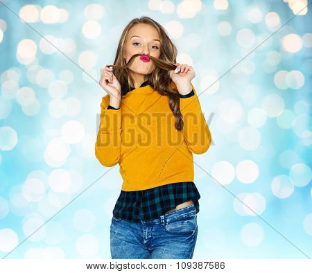 people, style and fashion concept - happy young woman or teen girl in casual clothes having fun making mustache of her hair strand over blue holidays lights background