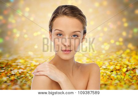 beauty, people, body care and health concept - smiling young woman face and hand on bare shoulder over golden holidays lights or yellow glitter background