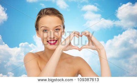 beauty, people, love, valentines day and make up concept - smiling young woman with pink lipstick on lips showing heart shape hand sign over blue sky and clouds background