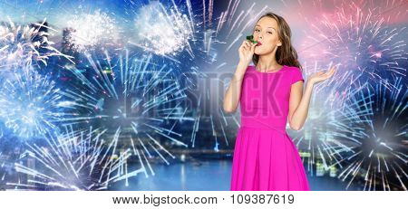 people, holidays and celebration concept - happy young woman or teen girl in pink dress and party cap over firework at night city background
