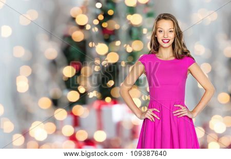 people, style, holidays and fashion concept - happy young woman or teen girl in pink dress over christmas tree lights background
