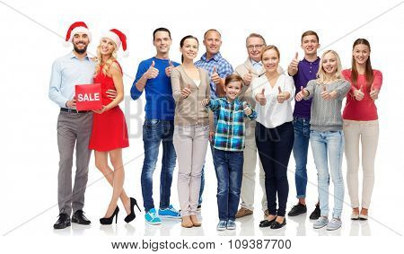 gesture, shopping, discount, christmas and people concept - group of happy people showing thumbs up and couple with sale sign