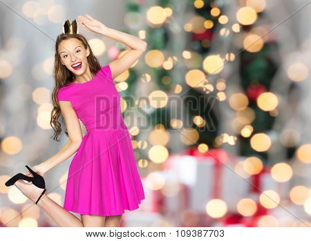 people, holidays and fashion concept - happy young woman or teen girl in pink dress and princess crown over christmas tree lights background