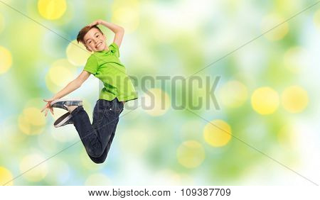 happiness, childhood, freedom, movement and people concept - smiling boy jumping in air over summer green holidays lights background