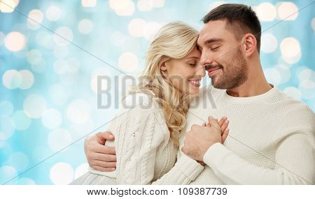 family, love, winter, holidays and people concept - happy couple over blue holidays lights background