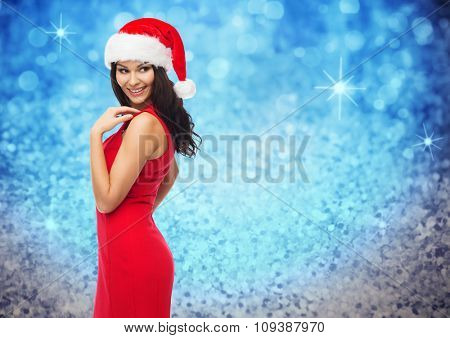 people, holidays, christmas and celebration concept - beautiful sexy woman in santa hat and red dress over blue glitter and lights background