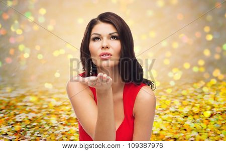 people, holidays and gesture concept - beautiful sexy woman in red dress sending blow kiss over golden glitter or holidays lights background