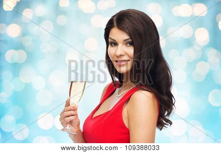 people, holidays, christmas and celebration concept - beautiful sexy woman in red dress with champagne glass over blue lights background