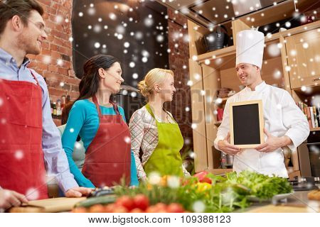 cooking class, culinary, food and people concept - happy friends and chef cook with blank menu chalk board in kitchen over snow effect