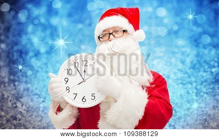 christmas, holidays, time and people concept - man in costume of santa claus with clock showing twelve pointing finger over blue glitter or lights background