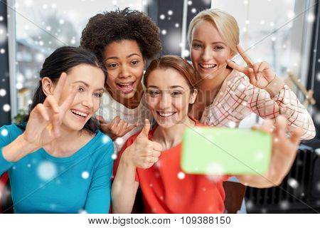 people, leisure, friendship, gesture and technology concept - happy young women taking selfie with smartphone and showing victory gesture over snow effect