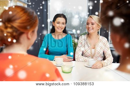 people, leisure, friendship and communication concept - happy young women meeting and drinking tea or coffee at cafe over snow effect