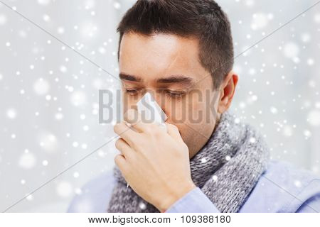 healthcare, flu, people, rhinitis and medicine concept - close up of ill man blowing his nose with paper napkin at home over snow effect