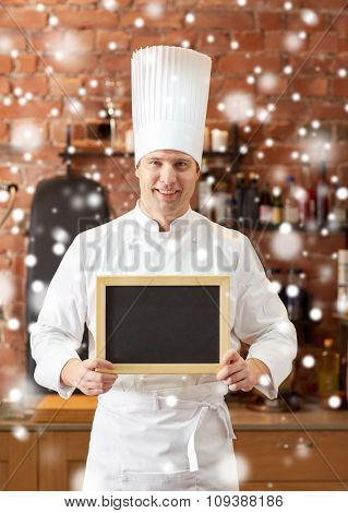 cooking and people concept - happy male chef cook with black blank menu chalk board in kitchen in restaurant kitchen over snow effect