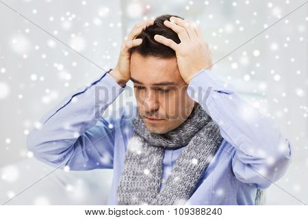 health care, people, winter and medicine concept - close up of ill man with flu suffering from headache at home over snow effect