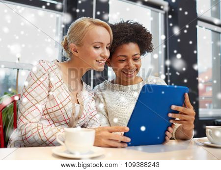 people, leisure, friendship and technology concept - happy young women with tablet pc computer drinking tea or coffee at cafe over snow effect