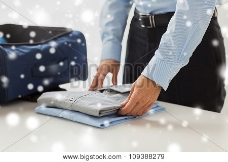 business, trip, luggage and people concept - close up of businessman packing clothes into travel bag over snow effect