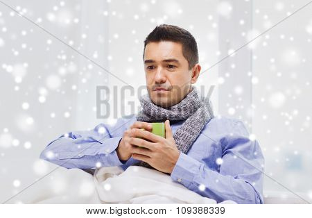 health care, people, winter and medicine concept - ill man with flu drinking hot tea from cup at home over snow effect