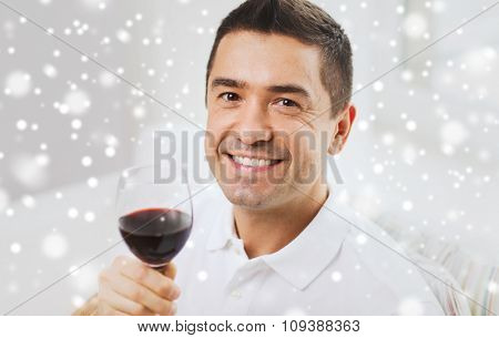 profession, drinks, leisure, holidays and people concept - happy man drinking red wine from glass over snow effect