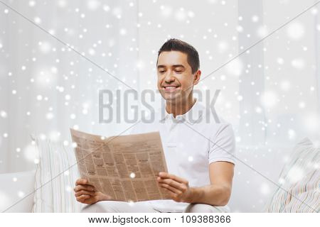 leisure, information, people and mass media concept - happy man reading newspaper at home with snow effect