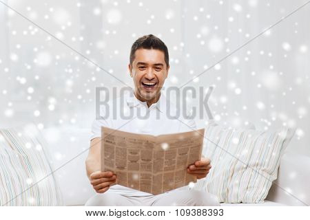 leisure, information, people and mass media concept - happy man reading newspaper and laughing at home with snow effect
