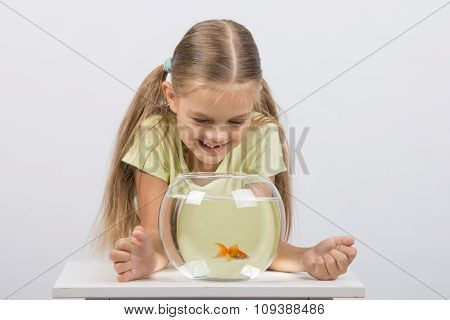 Happy Six Year Old Girl Looking Down On The Aquarium With Goldfish