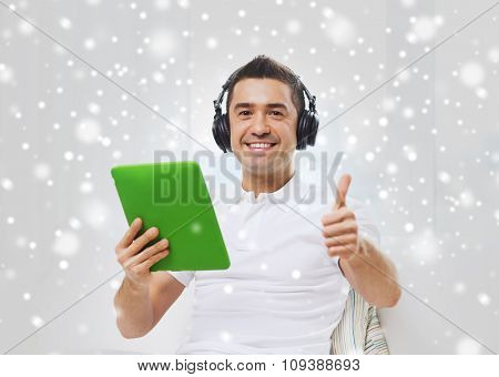 technology, people, lifestyle and distance learning concept - happy man with tablet pc computer and headphones listening to music and showing thumbs up at home over snow effect