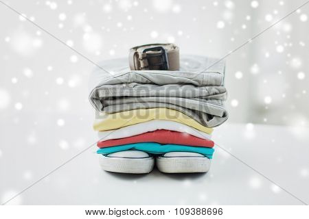 clothes, personal staff and objects concept - close up of folded shirts, pants, belt and shoes on table at home over snow effect