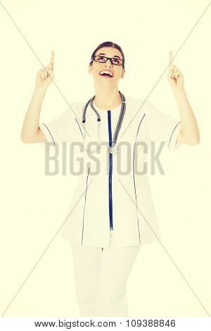 Happy female doctor pointing up.