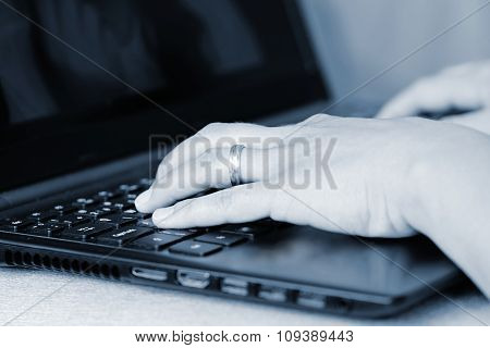 Hands on the keyboard. Office worker typing on the keyboard on the laptop.