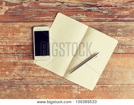 business, education, objects and technology concept - close up of notebook, pen and smartphone on table
