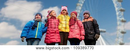 childhood, tourism, travel, vacation and people concept - happy little children outdoors over ferry wheel and blue sky background