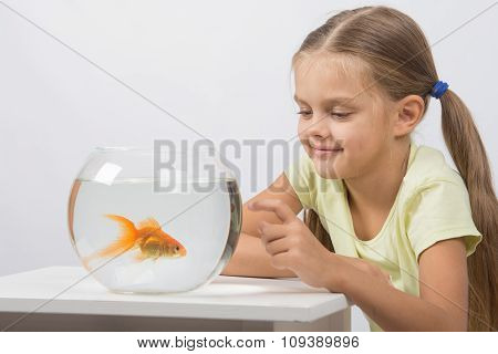 Happy Little Girl Knocking His Finger On The Aquarium With Goldfish