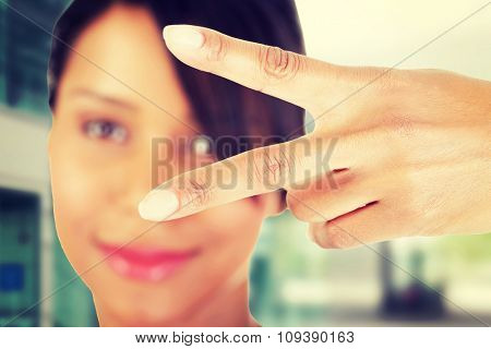 Happy young teenager girl showing victory sign.