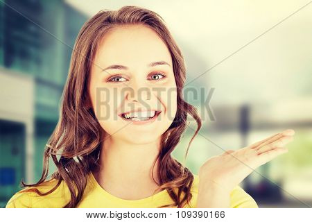 Happy , excited young woman presenting copy space on her palm