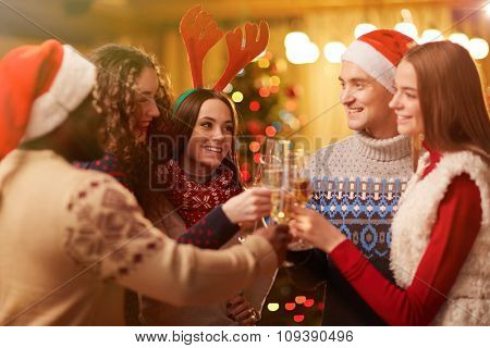 Happy young friends toasting on Christmas party
