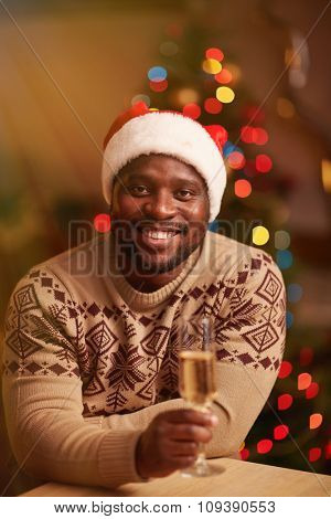 Happy guy with flute of champagne looking at camera