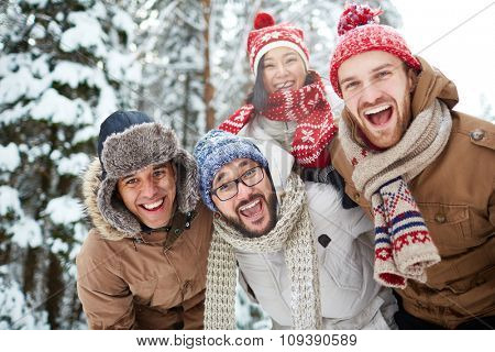 Joyful friends looking at camera in natural environment in winter