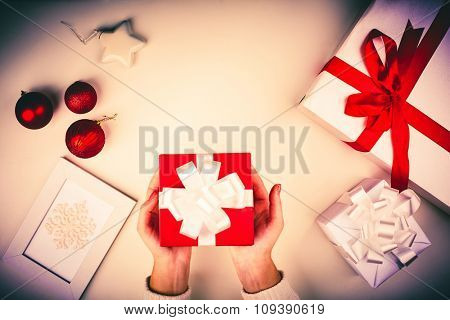 Human palms holding package with gift, giftboxes with Christmas presents and other symbols of holiday